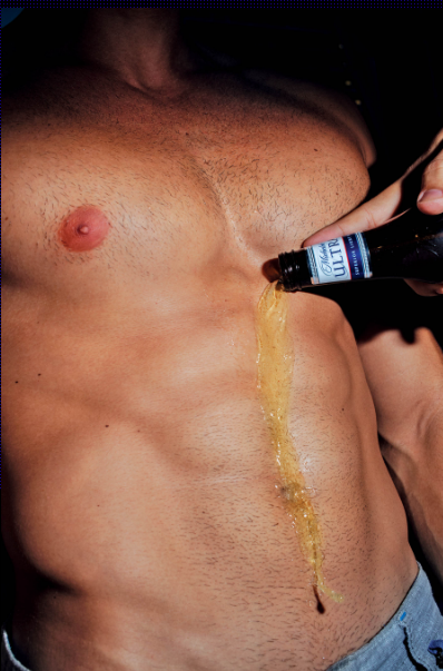 A stubbly chest and torso with a stream of yellow Michelob Ultra poured over it